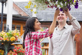 Couple touching flowers in hanging basket — Stock Photo