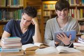 Mladý muž s tablet pc v knihovně — Stock fotografie