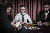 Serious man looking up from high stakes poker game — Stock Photo