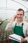 Worker taking notes and calling in greenhouse — Stock Photo