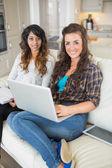 Sonrientes chicas que trabajan en portátil — Foto de Stock