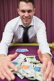 Happy man at poker table taking his winnings — Stock Photo