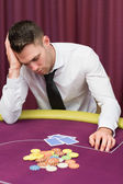 Man leaning on poker table looking disappointed — Stock Photo