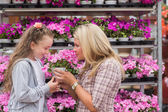 Mother and daughter smelling plant — Stock Photo