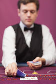 Dealer in a casino distributing cards — Stock Photo