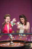 Women throwing chips on roulette table — Stock Photo