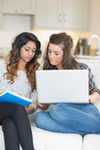 Girls doing homework with laptop — Stock Photo