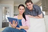 Jovem casal usando um computador tablet — Fotografia Stock