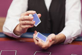 Dealer shuffling deck of cards in a casino — Stock Photo