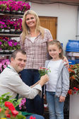 Mother and daughter receiving flower pot from employee — Stock Photo