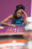 Woman looking upset at roulette table — Stock Photo