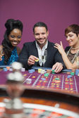 Man playing roulette with two women — Stock Photo