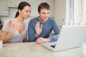 Couple using laptop for video chat and waving — Stock Photo