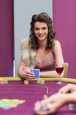 Woman sitting at the table smiling holding cards — Stock Photo