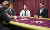Men looking up from high stakes poker game — Stock Photo