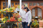 Happy couple looking at red plant — Stock Photo