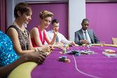 Sentado en la mesa de casino sonriendo — Foto de Stock