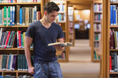 Man standing at the library holding a book — Stock Photo