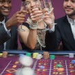 Stock Photo: Three toasting at roulette table