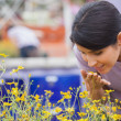Stock Photo: Womsmelling yellow flowers happily