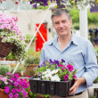 Stock Photo: Smiling customer taking flower boxes outside