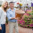 Happy couple holding ceramic flower pot — Stock Photo