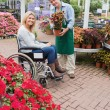 Smiling woman in wheelchair buying a flower - Stockfoto