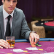 Man sitting at poker table with whiskey — Stock Photo #23090424