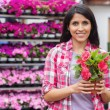 Woman standing in front of shelves and holding a flower — Stock Photo #23090458