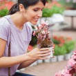 Woman raising a flower while smelling - ストック写真