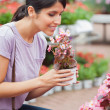Stock Photo: Womraising flower while smelling