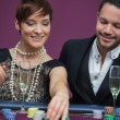 Stock Photo: Womplacing roulette bet with man