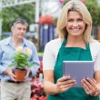 Smiling woman holding a tablet pc with customer holding plant be - Stok fotoğraf