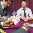 Man at poker table has royal flush — Stock Photo