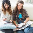 Two friends sitting on couch doing homework — Stock Photo