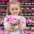 Little girl smiling and holding a flower pot — Stock Photo