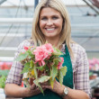 blonde woman holding a flower working in garden center — Stock Photo