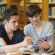 Stock Photo: Student showing another something on tablet in library