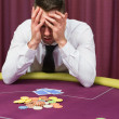 Man holding head in hands at poker table - Stock Photo