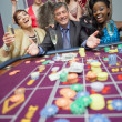 Women celebrating man's success at roulette — Foto Stock