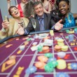 Women celebrating man's success at roulette - Stok fotoğraf