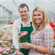 Woman choosing a flower in greenhouse with employee — Stock Photo #23091504