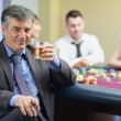 Man drinking whiskey at roulette table — Stock Photo