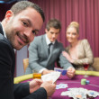 Man smiling and looking up from poker game — Stock Photo #23091532