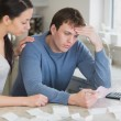Worried couple looking over bills — Stock Photo