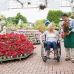 Woman in wheelchair talking to employee — Stock Photo
