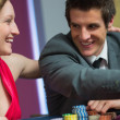 Stock Photo: Couple smiling at each other at roulette table