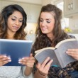 Two girls reading a book and holding a tablet computer — Stock Photo