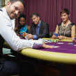 Smiling dealer at poker game — Stock Photo #23091870