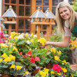 Garden center worker holding yellow flower — Stock Photo